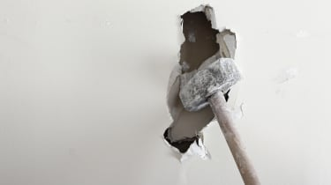 A sledgehammer smashing through a white wall