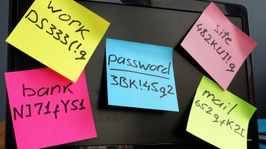 Sticky notes on a monitor displaying assorted passwords