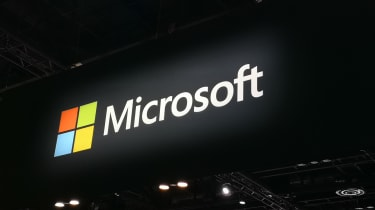 Microsoft logo suspended above a conference floor
