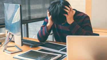 A young professional showing signs of stress at work