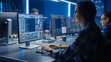 Female IT programmer working on a desktop computer in data centre