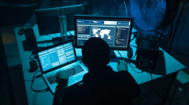 Image of a cyber criminal using several computers in a dark room