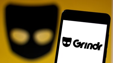 The Grindr app on a smartphone in front of a background of its logo