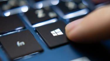 The Windows key being pushed on a blue laptop