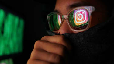 A hacker with Instagram's logo reflected in his glasses