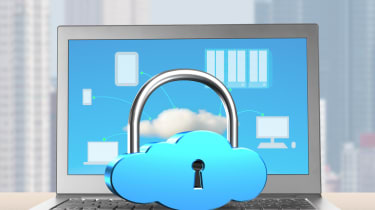 Cloud padlock resting on laptop with city skyline behind
